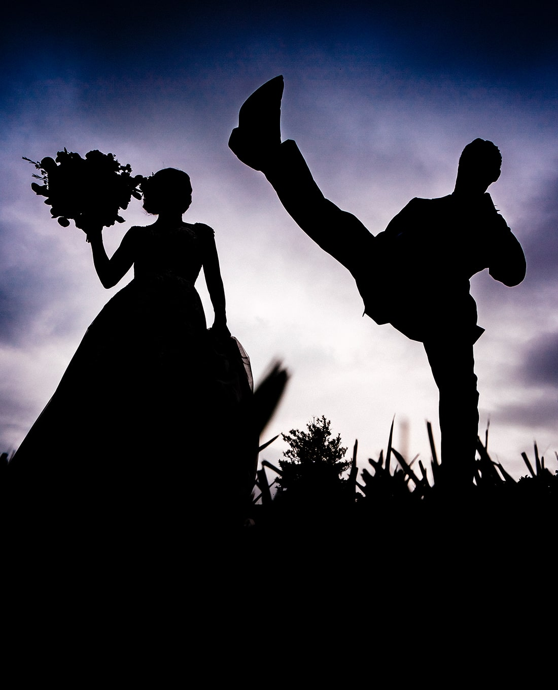 A colorful, candid, silhouetted picture of a bride holding her bouquet out to her side as her groom karate kicks towards the camera on their Kansas City wedding day at The Bowery Event Space.