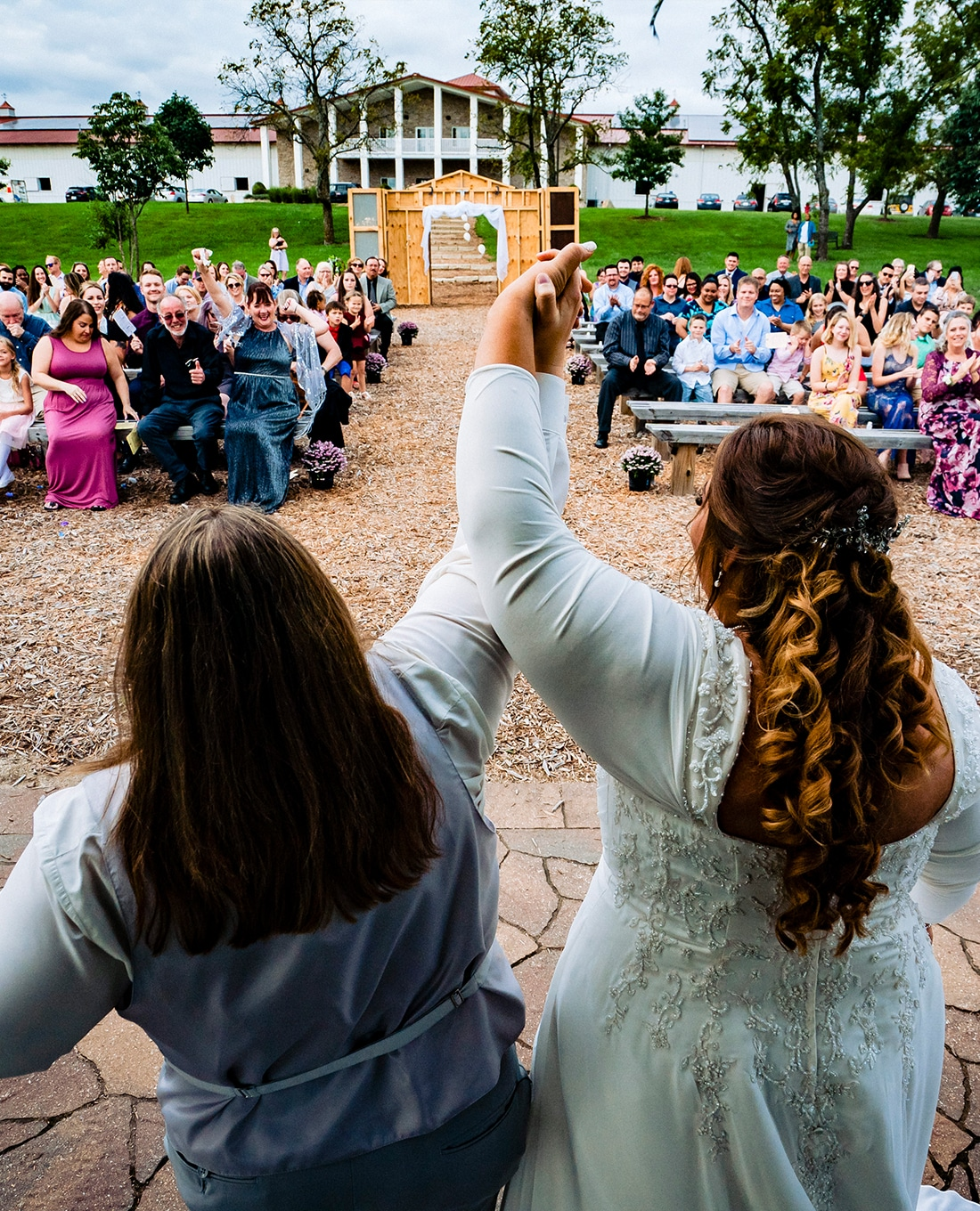 A colorful, candid picture taken from behind two brides as they raise their arms in victory at the end of their wedding ceremony, as their family and friends cheer them on.