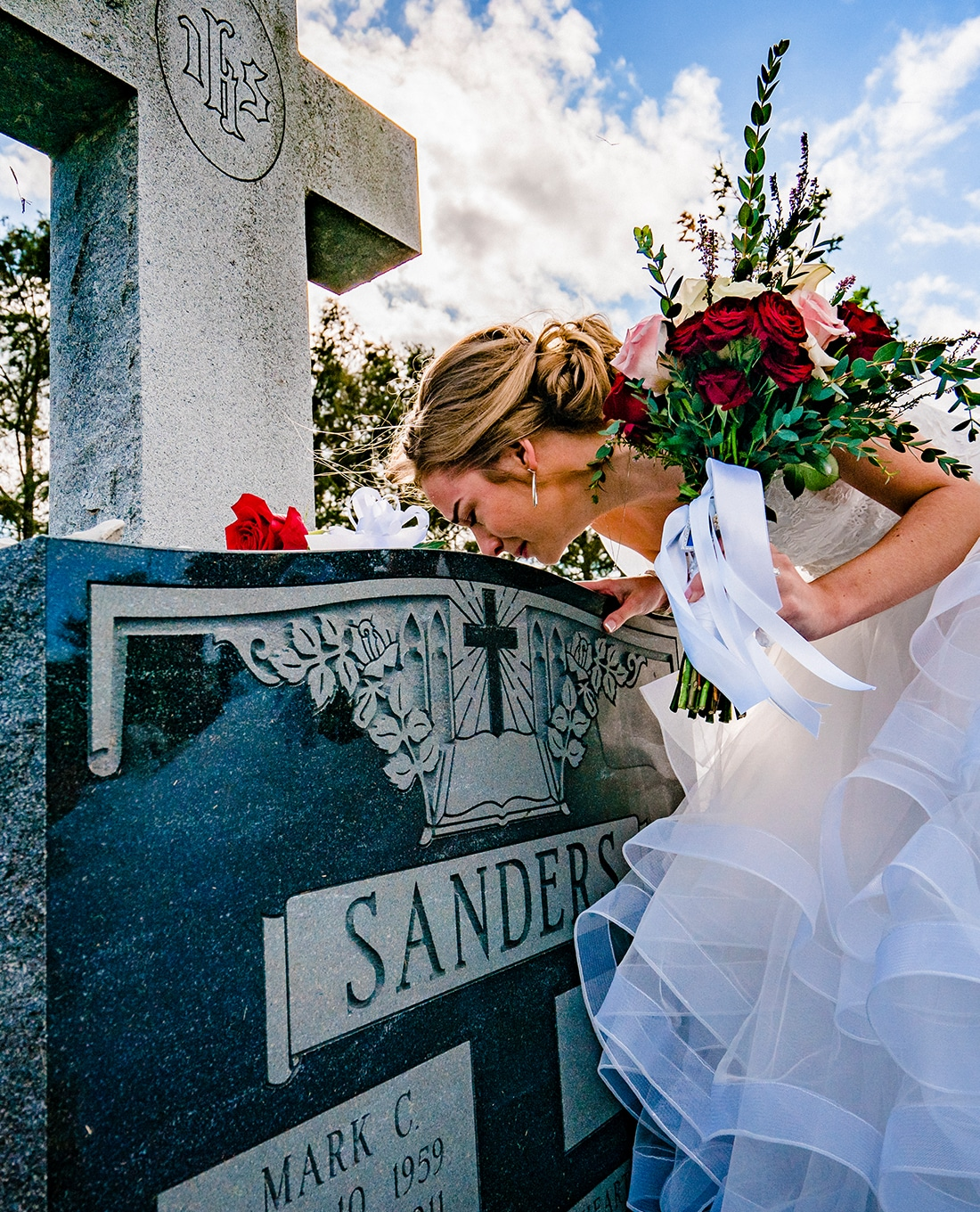 A colorful, candid picture of a bride leaning down to kiss the top of her fathe's gravestone on her sunny wedding day.