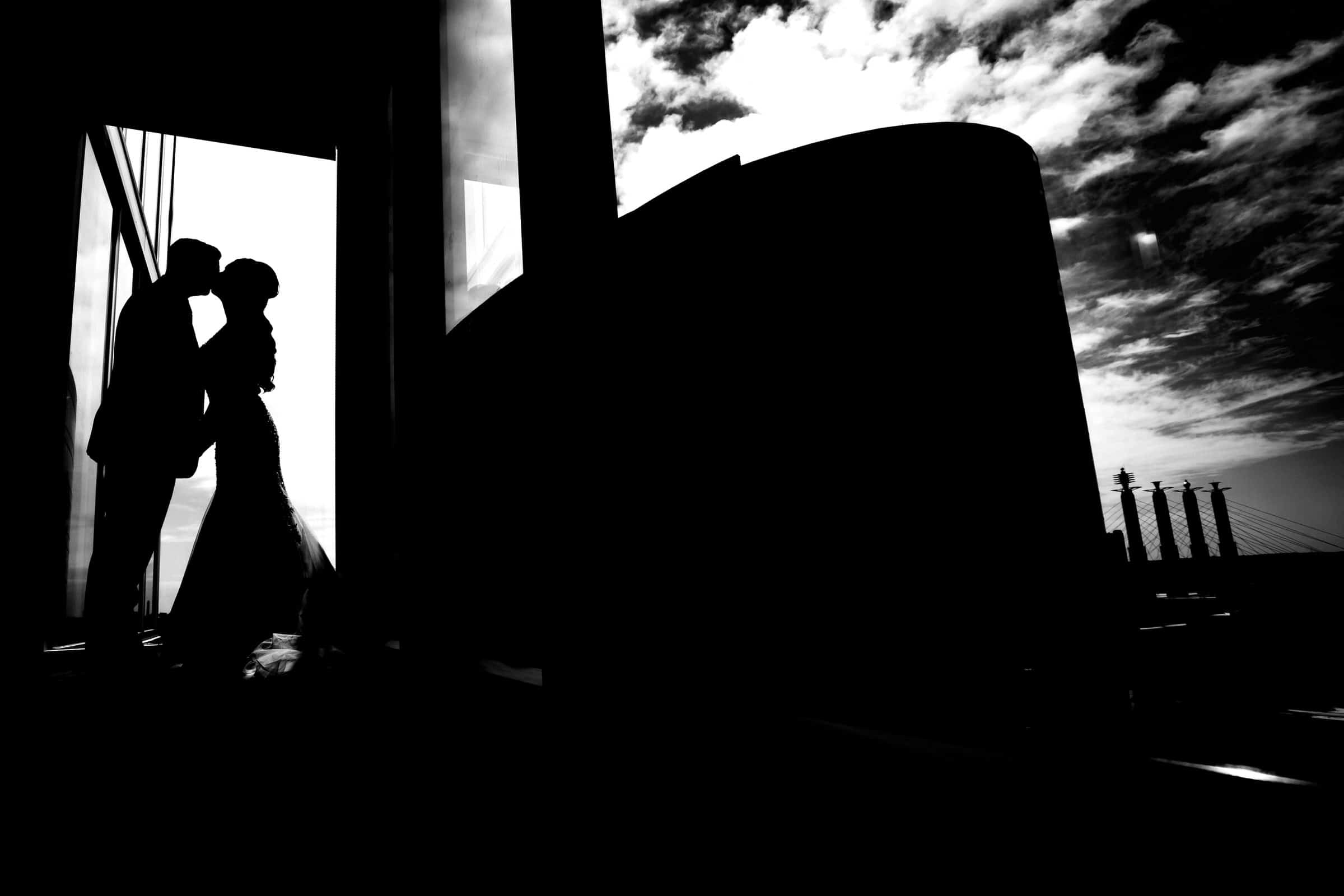A bold black and white picture of a bride and groom silhouetted in a window in a highi-rise, with the kansas city background visible out the window behind them.