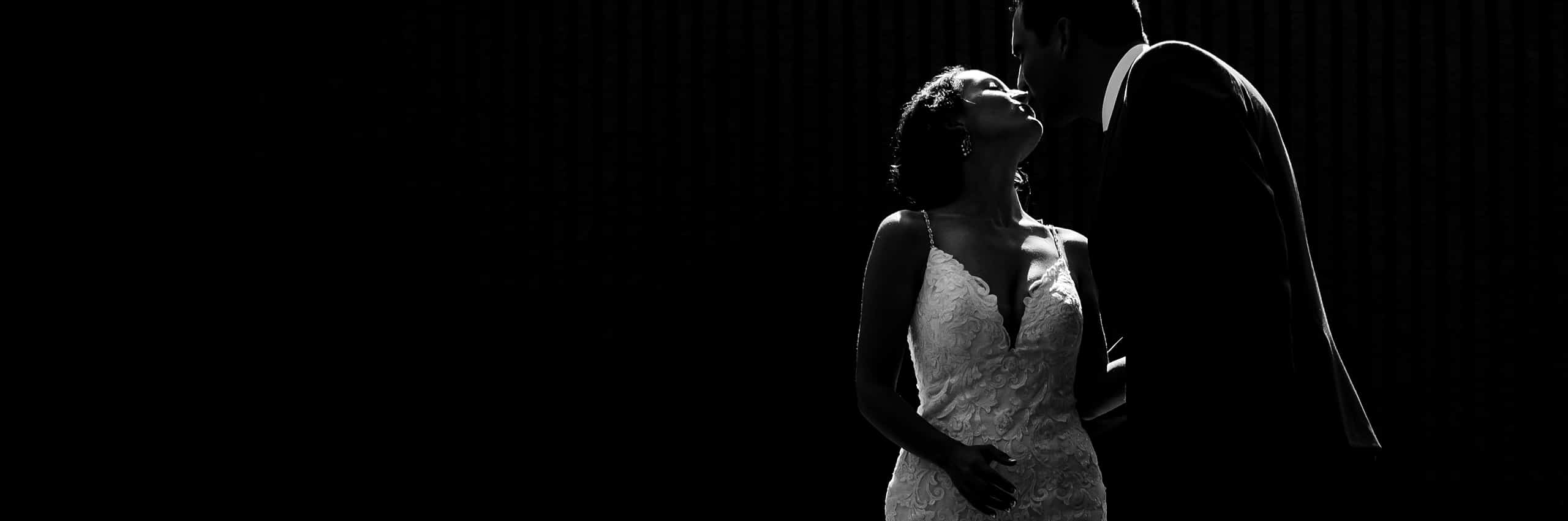 A bold black and white candid picture of a groom leaning down to kiss his bride, the outlines of their bodies lit by sunlight.
