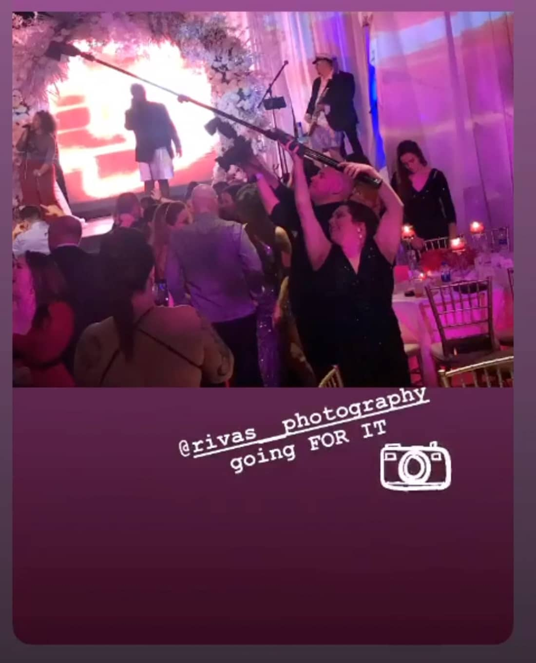A screenshot of an Instagram post of two photographers in the middle of a crowd, holding camera and lightstand up.