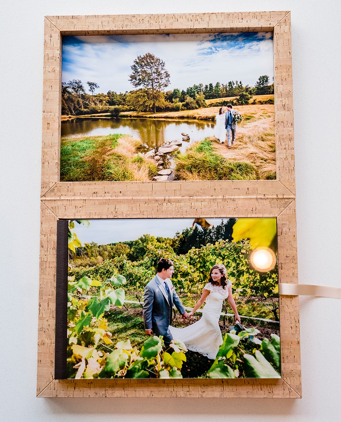 A staged photo of a wedding album with a reflective cover housed in a cork box sitting on a white table.