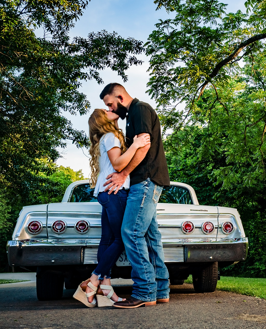 A colorful picture of a man and woman standing behind a 1970 Impala, sharing an embrace and kiss during their summer engagement session in Kansas City.