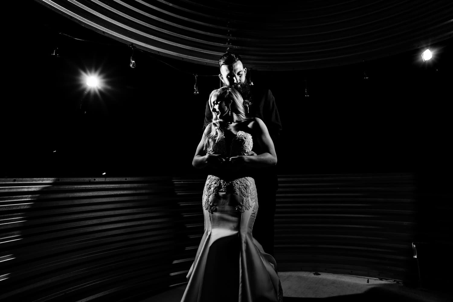 A dramatic black and white picture of a bride and groom sharing an embrace on their wedding night.